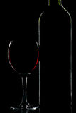 Silueta de la botella y del vidrio de vino sobre negro Foto de archivo
