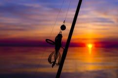 Silueta de la caña de pescar con cebo en fondo de la puesta del sol imágenes de archivo libres de regalías