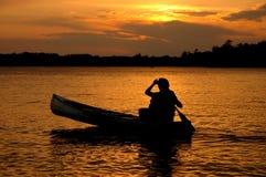 Silueta de la canoa en puesta del sol Foto de archivo