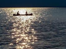 Silueta de la canoa - sol poniente de oro chispeante de la cinta Imagen de archivo libre de regalías