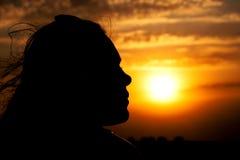 Silueta de la cara de la chica joven que mira en el cielo nublado hermoso Foto de archivo libre de regalías