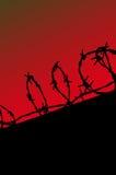 Silueta de la cerca de la prisión en el cielo rojo del gradiente Imágenes de archivo libres de regalías