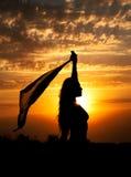 Silueta de la chica joven con el mantón en fondo del cielo nublado hermoso con puesta del sol amarillo-naranja Fotografía de archivo libre de regalías