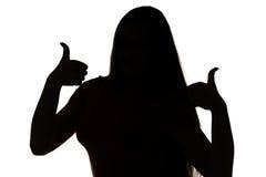 Silueta de la chica joven con los pulgares Foto de archivo