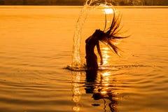 Silueta de la chica joven en el agua con el chapoteo Foto de archivo