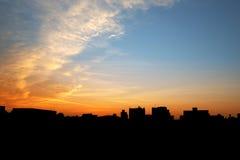 Silueta de la ciudad debajo del cielo de la mañana Fotos de archivo