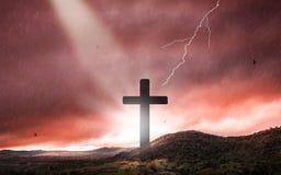 Silueta de la cruz del crucifijo en el tiempo de la puesta del sol con el fondo santo de la luz y de la tempestad de truenos fotos de archivo