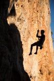 Silueta de la ejecución del escalador de roca en las montañas del againstthe de la cuerda del belay Foto de archivo