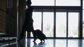 Silueta de la empresaria con la maleta en un hotel metrajes