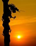 Silueta de la estatua del dragón del estilo chino con puesta del sol Fotos de archivo