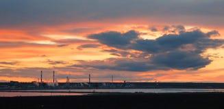 Silueta de la fábrica industrial en el espejo de la puesta del sol en agua Foto de archivo libre de regalías