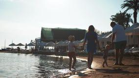 Silueta de la familia activa que se divierte y que disfruta de unidad en la playa en la puesta del sol almacen de metraje de vídeo
