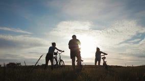 Silueta de la familia del motorista, padres con dos ni?os en las bicis en la puesta del sol Concepto de familia amistosa almacen de video
