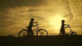 Silueta de la familia del motorista, padres con dos ni?os en las bicis en la puesta del sol Concepto de familia amistosa metrajes