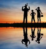Silueta de la familia en el cielo de la puesta del sol. imagen de archivo