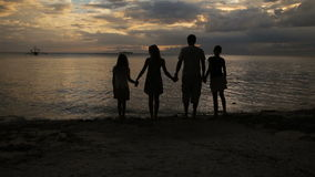 Silueta de la familia en la playa en la puesta del sol almacen de metraje de vídeo