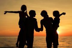 Silueta de la familia feliz que juega en la playa en el sunse Foto de archivo