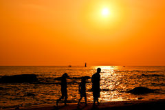 Silueta de la familia que recorre en la playa Imágenes de archivo libres de regalías