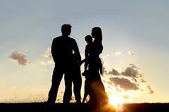 Silueta de la familia y del perro felices afuera en la puesta del sol Fotografía de archivo libre de regalías
