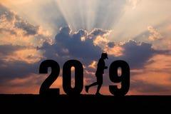 Silueta de la Feliz Año Nuevo 2019 en la puesta del sol Imágenes de archivo libres de regalías