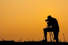 Silueta de la foto del tiroteo del fotógrafo para una salida del sol Imagenes de archivo