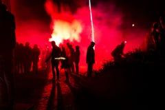 Silueta de la gente con los fuegos artificiales Foto de archivo
