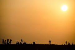 Silueta de la gente en la puesta del sol Fotografía de archivo libre de regalías