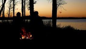 Silueta de la gente enjoyiing la hoguera hermosa de la orilla del lago enseguida después de la puesta del sol con los árboles a l almacen de metraje de vídeo