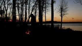 Silueta de la gente enjoyiing la hoguera hermosa de la orilla del lago enseguida después de la puesta del sol con los árboles a l almacen de video
