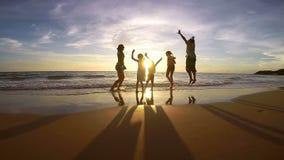 Silueta de la gente feliz que juega en la playa en el tiempo de la puesta del sol metrajes