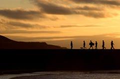 Silueta de la gente que recorre en la puesta del sol Foto de archivo