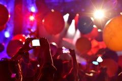 Silueta de la gente que toma las fotos con los teléfonos elegantes en la estafa viva Imagen de archivo