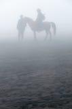 Silueta de la gente y de caballos en niebla o niebla Imagen de archivo libre de regalías