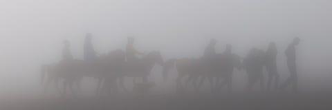 Silueta de la gente y de caballos en niebla o niebla Foto de archivo