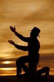 Silueta de la genuflexión del vaquero ambas manos para arriba Imagen de archivo libre de regalías