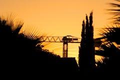 Silueta de la grúa y de árboles durante una puesta del sol Fotos de archivo libres de regalías