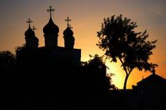 Silueta de la iglesia ortodoxa y del abedul en la puesta del sol Imagenes de archivo