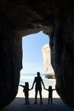 Silueta de la madre con dos niños en una cueva en la playa del túnel Foto de archivo