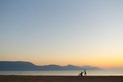 Silueta de la madre con el cochecito que disfruta de maternidad en la puesta del sol Foto de archivo