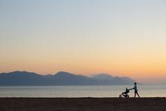 Silueta de la madre con el cochecito que disfruta de maternidad en la puesta del sol Fotografía de archivo