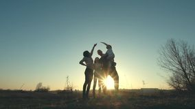 Silueta de la madre, del padre y de las hijas divirtiéndose en la puesta del sol metrajes