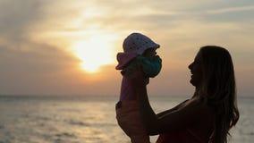 Silueta de la madre que besa al bebé en la puesta del sol cerca metrajes