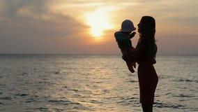 Silueta de la madre que besa al bebé en la puesta del sol cerca almacen de metraje de vídeo