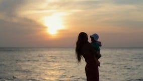 Silueta de la madre que detiene al bebé mientras que se coloca almacen de metraje de vídeo