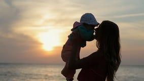 Silueta de la madre que detiene al niño en las manos en almacen de metraje de vídeo