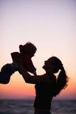 Silueta de la madre que juega con el bebé en puesta del sol Imagenes de archivo