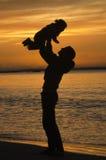 Silueta de la madre que levanta aquí al niño en la puesta del sol Imágenes de archivo libres de regalías