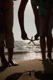 Silueta de la madre y de la hija que cogen una estrella de mar en la playa Fotos de archivo