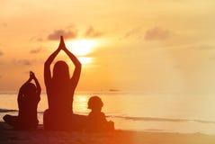 Silueta de la madre y de los niños que hacen yoga en la puesta del sol Imagen de archivo
