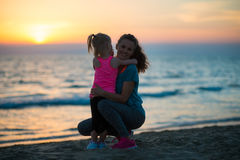 Silueta de la madre y del bebé en la playa Imagen de archivo